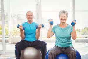 man and woman on balls at fitness center using weights