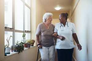 Female nurse walking with senior woman