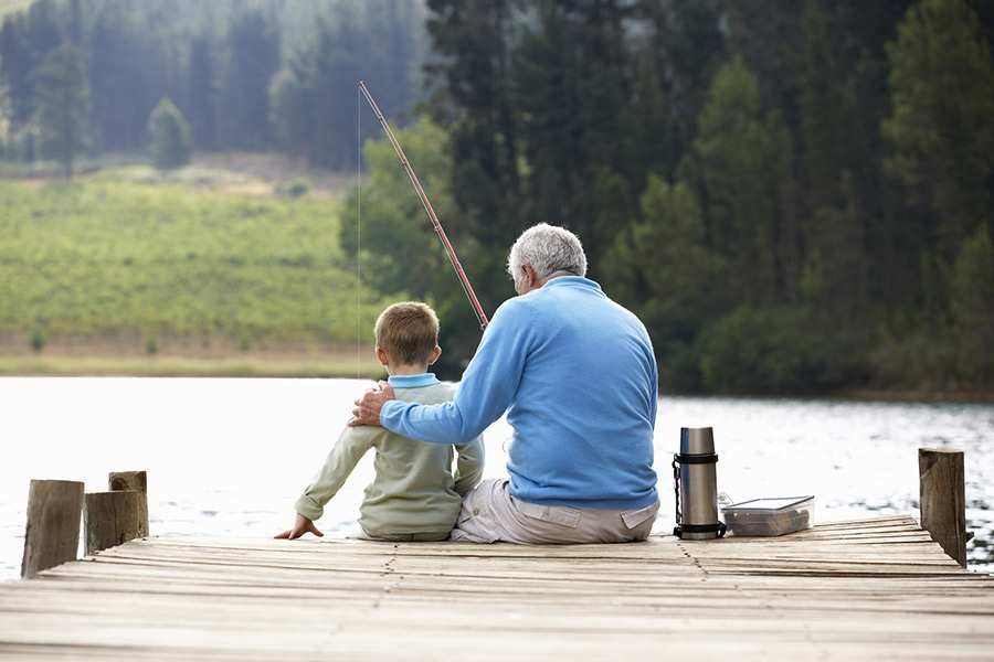 Senior man fishing with his grandson sitting on a dock