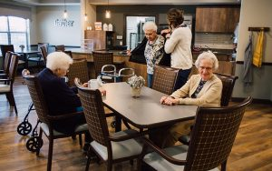 Woodland Memory Care residents in a Pelican Landing Community room