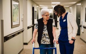 Pelican Landing employee walking with resident in Woodland memory care unit