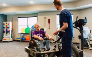 Pelican Landing Physical therapist assisting resident